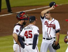 Atlanta Braves starting pitcher Mike Minor (36) wipes his face as he talks with pitching coach Roger McDowell (45) and catcher Evan Gattis after loading the bases in the sixth inning of a baseball game against the Philadelphia Phillies Tuesday, Sept. 2, 2014, in Atlanta. (AP Photo/John Bazemore)