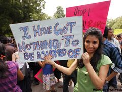 A woman holds a placard at the Slutwalk in New Delhi, India, on July 31, where there were no short skirts or fishnet stockings to photograph.