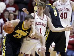 Iowa forward Eric May is fouled by Indiana guard Jordan Hulls as they get tangled up in the second half of an NCAA college basketball game in Bloomington, Ind., Saturday, March 2, 2013. Indiana defeated Iowa 73-60. (AP Photo/Michael Conroy)