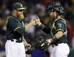 Oakland Athletics reliever Sean Doolittle, left, high-fives catcher Derek Norris at the end of a 9-5 win over the Los Angeles Angels during a baseball game on Friday, May 30, 2014, in Oakland, Calif. (AP Photo/Marcio Jose Sanchez)