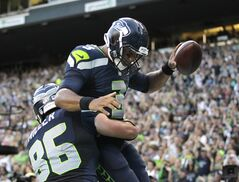 Seattle Seahawks' Zach Miller (86) lifts quarterback Russell Wilson up after Wilson scored on a run against the Chicago Bears in the first half of a preseason NFL football game, Friday, Aug. 22, 2014, in Seattle. (AP Photo/John Froschauer)