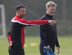 FILE - In this Monday, March 31, 2014 file photo Manchester United's manager David Moyes, right, stands alongside Ryan Giggs as the team trains at Carrington training ground in Manchester. Manchester United says manager David Moyes has left the Premier League club after less than a year in charge, amid heavy speculation he was about to be fired. United released a brief statement in its website Tuesday, saying the club