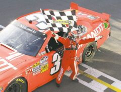 Justin Allgaier waves a checkered flag in celebration after winning the NAPA Auto Parts 200 NASCAR Nationwide race in Montreal on Saturday.