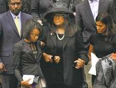 Ebert's widow, Chaz Ebert (centre) leaves Holy Name Cathedral after his funeral in Chicago.
