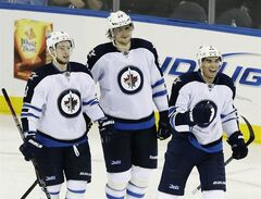 Winnipeg Jets' Evander Kane, right, reacts after scoring a goal as teammates Alex Burmistrov, left, and Nik Antropov watch during the third period of an NHL hockey game against the New York Rangers Tuesday, Feb. 26, 2013, in New York. The Jets won the game 4-3. (AP Photo/Frank Franklin II)