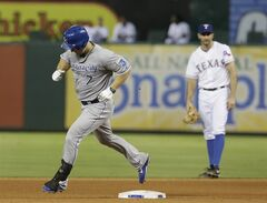 CORRECTS TO FOURTH INNING NOT SECOND INNING - Kansas City Royals' Josh Willingham (7) rounds the bases on his solo home run as Texas Rangers shortstop Adam Rosales (9) looks on during the fourth inning of a baseball game Friday, Aug. 22, 2014, in Arlington, Texas. (AP Photo/LM Otero)