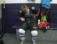 Six-year-old Shane Buchan gets dressed for hockey practice in Oakville, Ont., Friday, Oct.5, 2012. A little noticed tariff change on imports in the budget is likely to fatten Ottawa's coffers for years to come, but wind up costing Canadian consumers.The federal government made much of a shiny bauble in the budget that eliminated tariffs on sporting and athletic equipment such as hockey pants and gloves as well as baby clothes.THE CANADIAN PRESS/Richard Buchan