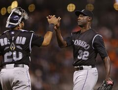 Colorado Rockies pitcher LaTroy Hawkins, right, celebrates with catcher Wilin Rosario after defeating the San Francisco Giants in San Francisco, Friday, June 13, 2014. (AP Photo/Beck Diefenbach)