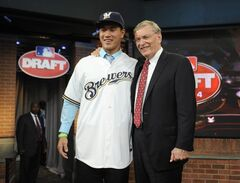 Baseball commissioner Bud Selig, right, poses with pitcher Kodi Medeiros from Waiakea High School in Hilo, Hawaii, who was selected by the Milwaukee Brewers with the 12th selection in the 2014 MLB baseball draft Thursday, June 5, 2014, in Secaucus, N.J. (AP Photo/Bill Kostroun)