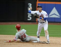 New York Mets shortstop Wilmer Flores, right, forces out Philadelphia Phillies' Chase Utley (26) and throws to first base to complete the double play in the ninth inning of a baseball game on Sunday, Aug. 31 2014, in New York. (AP Photo/Kathy Kmonicek)