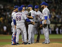 New York Mets' Dillon Gee, center, is visited by pitching coach Dan Warthen and infield players in the fourth inning of a baseball game against the Oakland Athletics on Tuesday, Aug. 19, 2014, in Oakland, Calif. (AP Photo/Ben Margot)