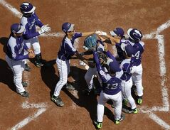 South Korea's Jae Yeong Hwang is mobbed by teammates after hitting a home run during the third inning of an International baseball game against Puerto Rico at the Little League World Series, Sunday, Aug. 17, 2014, in South Williamsport, Pa. (AP Photo/Matt Slocum)