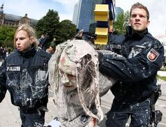 A paint spattered supporter of the Frankfurt Occupy Camp is taken away by police officers during the removal of the occupy camp in front of the European Central Bank in Frankfurt, Germany, Wednesday, May 16, 2012. The camp which has been occupied for eight months, was cleared ahead of the so called
