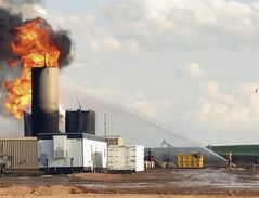 In this Monday, July 7, 2014 photo, firefighters battle a blaze caused by a lightning strike at a saltwater disposal facility near Alexander, N.D. In just over a month, lightning strikes have destroyed three of the state's more than 440 saltwater disposal facilities. Saltwater is a byproduct of oil production. (AP Photo/Josh Wood)