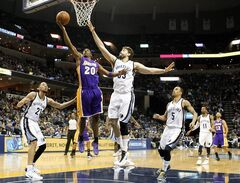 Los Angeles Lakers guard Jodie Meeks (20) goes to the basket against Memphis Grizzlies defenders Marc Gasol (33), of Spain, Tayshaun Prince (21), Courtney Lee (5) in the first half of an NBA basketball game, Wednesday, Feb. 26, 2014, in Memphis, Tenn. (AP Photo/Lance Murphey)