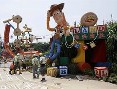 FILE - In this Sept. 8, 2011 file photo, workers walk past Toy Story character Woody at the construction site of the new attraction area Toy Story Land in Hong Kong Disneyland. Disneyland in the southern Chinese city of Hong Kong has turned a profit for the first time since it opened in 2005. The park said Monday, Feb. 18, 2013, it earned 109 million Hong Kong dollars ($14 million) in 2012. (AP Photo/Kin Cheung, File)