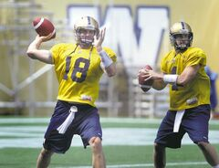 New No. 1 quarterback Justin Goltz (18) and new No. 3 QB Buck Pierce, formerly No. 1, toss footballs Friday at practice as they prepare for Monday's game against the B.C. Lions in Vancouver.