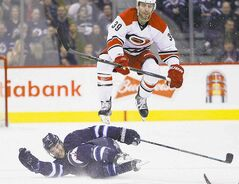 Carolina's Patrick Dwyer leaps over Winnipeg's Matt Halischuk.