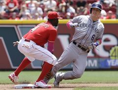 Cincinnati Reds second baseman Brandon Phillips (4) tags out Colorado Rockies' Corey Dickerson (6) trying to steal second base in the fourth inning of a baseball game, Sunday, May 11, 2014, in Cincinnati. (AP Photo/Al Behrman)