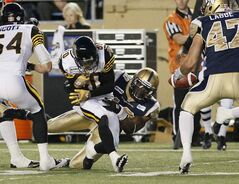 Bombers' Henoc Muamba (10) forces the fumble as he takes down Hamilton Tiger-Cats' Chris Williams (80) during the second half.