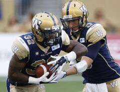 Winnipeg Blue Bombers' quarterback Drew Willy (5) hands off to Nic Grigsby (32) during the first half of CFL action against the Toronto Argonauts in Winnipeg Thursday.