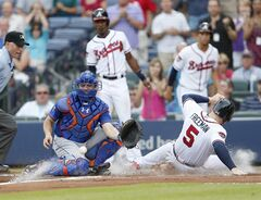 Atlanta Braves' Freddie Freeman (5) scores on a Chris Johnson three-run double as New York Mets catcher Travis d'Arnaud, second from left, waits for the throw in the first inning of a baseball game in Atlanta, Wednesday, July 2, 2014. (AP Photo/John Bazemore)