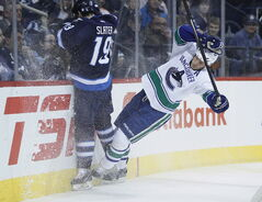 The Jets' Jim Slater played a physical game Wednesday, seen here colliding with the Canucks' Kevin Bieksa.