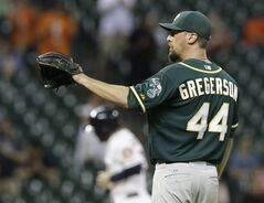 Oakland Athletics relief pitcher Luke Gregerson reaches for the ball as Houston Astros' Jose Altuve, background, rounds the bases on a Chris Carter three-run homer in the eighth inning of a baseball game Tuesday, Aug. 26, 2014, in Houston. The Astros won 4-2. (AP Photo/Pat Sullivan)