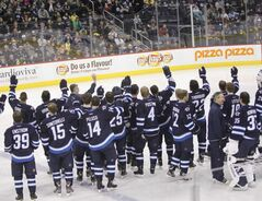 After the official team picture was taken Friday morning, Winnipeg Jets players and coaches wave to fans in the MTS Centre attending the optional team practice.