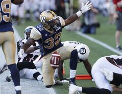 Winnipeg Blue Bombers' Nic Grigsby (32) disputes an out-of-bounds call in the Ottawa Redblacks' end zone during the first half of CFL action in Winnipeg Thursday, July 3, 2014. Grigsby has been quite a find for the Blue Bombers.The five-foot-11, 195-pound running back has played a big role in Winnipeg opening the season 2-0. THE CANADIAN PRESS/John Woods