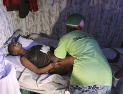 FILE- In this July 25, 2010 file photo, traditional birth attendant Magret Atieno assists Mary Wairimu into a position to give birth, during labor in the Korogocho neighborhood of Nairobi, Kenya. In the past decade, billions of dollars have been spent trying to save mothers in developing countries using strategies deemed essential by the United Nations. But in two large analyses of maternal health programs_ including one conducted by the U.N. itself _ the efforts appeared almost useless, raising troubling questions about how billions of dollars are spent. Critics are calling for the pricey global initiatives to be significantly overhauled; the programs continue to be implemented despite little proof they work. Even public health officials acknowledge they were taken aback by the results. (AP Photo/Khalil Senosi, File)