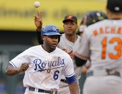 Kansas City Royals' Lorenzo Cain (6) gets caught in a rundown between Baltimore Orioles second baseman Jonathan Schoop, back, and third baseman Manny Machado (13) during the second inning of a baseball game at Kauffman Stadium in Kansas City, Mo., Saturday, May 17, 2014. Cain was tagged out by Machado. (AP Photo/Orlin Wagner)