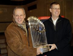 FILE - In this Nov. 23, 2013 file photo, Boston Red Sox CEO Larry Lucchino, left, and Chief Operating Officer Sam Kennedy hold the 2013 World Series baseball trophy on the red carpet at the Wang Theatre before a screening of a DVD about the series in Boston. Lucchino said Friday, Feb. 21, 2014, that he views the big-spending New York Yankees and his more frugal team as