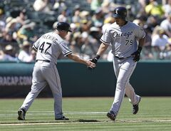 Chicago White Sox's Jose Abreu, right, is congratulated by third base coach Joe McEwing after Abreu hit a three-run home run off Oakland Athletics' Luke Gregerson in the eighth inning of a baseball game Wednesday, May 14, 2014, in Oakland, Calif. (AP Photo)