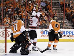 New Jersey Devils' David Clarkson, center, celebrates after scoring a goal against Philadelphia Flyers' Ilya Bryzgalov, left, of Russia, and Kimmo Timonen, of Finland, in the first period of Game 5 of a second-round NHL hockey Stanley Cup playoff series, Tuesday, May 8, 2012, in Philadelphia. (AP Photo/Matt Slocum)