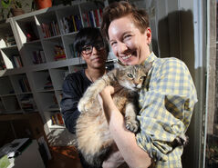 Angela Failler, right, and her partner Karen Sharma give some attention to Ella, their 14-year-old arthritic cat.