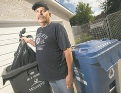 Stan Wilchuk stands with the garbage bins that were missed for pickup the last two weeks.