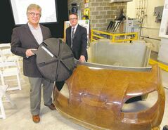 Joe Hogue of flax processor SWM (left) and Sean McKay, executive director of the Composites Innovation Centre. Hogue shows a farm-equipment cap and McKay displays a car body made from natural fibres.