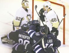Winnipeg Jets celebrate a goal by captain Andrew Ladd (right) during the second period against the Pittsburgh Penguins at the MTS Centre on Friday.