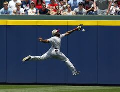 Boston Red Sox outfielder Jackie Bradley cannot reach a 2-RBI double hit over his head by Atlanta Braves' Justin Upton during the third inning of a baseball game on Monday, May 26, 2014, in Atlanta, Ga. (AP Photo/Butch Dill)