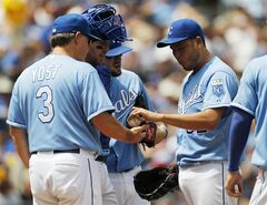 Kansas City Royals pitcher Bruce Chen (52) hands the baseball off to manager Ned Yost (3) as he leaves the game in the fifth inning against the Detroit Tigers at Kauffman Stadium in Kansas City, Mo., Sunday, July 13, 2014. Looking on are catcher Brett Hayes and third baseman Mike Moustakas. (AP Photo/Colin E. Braley)