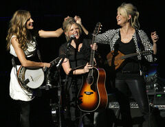 Emily Robison, left, and Martie Maguire, right, adjust Natalie Maines' hair as the Dixie Chicks perform at the new Nokia Theatre in Los Angeles.