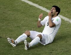 Uruguay's Luis Suarez reacts while sitting on the pitch during the group D World Cup soccer match between Italy and Uruguay at the Arena das Dunas in Natal, Brazil, Tuesday, June 24, 2014. (AP Photo/Hassan Ammar)