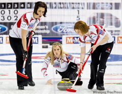 Team Canada skip Jennifer Jones deliver the rock as lead Dawn Askin (right) and second Jill Officer prepare to sweep in the game against Latvia Monday. Jones won 12-6.