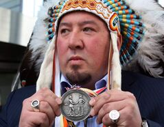 Grand Chief Derek Nepinak of the Assembly of Manitoba Chiefs displays a treaty medal during a protest on Parliament Hill on Jan. 11.