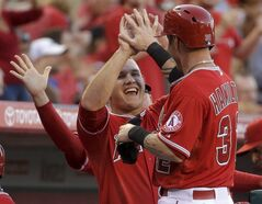 Los Angeles Angels' Mike Trout, left, greets Josh Hamilton in the dugout after he scored on a single by Howie Kendrick during the first inning of a baseball game against the Minnesota Twins in Anaheim, Calif., Tuesday, June 24, 2014. (AP Photo/Chris Carlson)