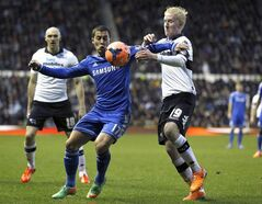 Chelsea's Eden Hazard, left, challenges for the ball with Derby's Will Hughes in Derby, England, Jan. 5, 2014. THE CANADIAN PRESS/AP, Kirsty Wigglesworth