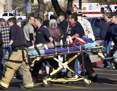 FILE - In this Jan. 8, 2011 file photo, Emergency personnel and Daniel Hernandez, an intern for U.S. Rep. Gabrielle Giffords, second right, move Giffords after she was shot in the head outside a shopping center in Tucson, Ariz. Hundreds of pages of police reports in the investigation of the shooting rampage were released Wednesday, March 27, 2013 marking the public's first glimpse into documents that authorities have kept private since the attack more than two years ago. (AP Photo/James Palka, File)