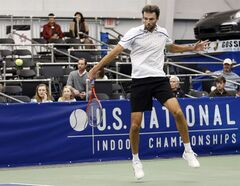 Ivo Karlovic, of Croatia, hits a backhand return to Kei Nishikori, of Japan, in the singles final at the U.S. National Indoor Tennis Championships on Sunday, Feb. 16, 2014, in Memphis, Tenn. (AP Photo/Rogelio V. Solis)