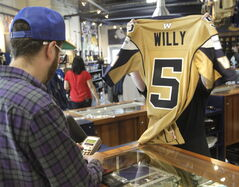 The day after the Winnipeg Blue Bombers won over the Toronto Argonauts at the home opener, Quarterback Drew Willy #5 jerseys are a big seller at the Bomber Store at Investors Group Field. Here, Bryce Twerdochlib purchases one.